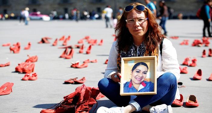 Nhà hoạt động nữ quyền Elizabeth Machuca Campos mang đến quảng trường Zocalo bức chân dung của chị gái Eugenia Machuca Campos bị sát hại năm 2017 và đôi giày chị mang khi thiệt mạng