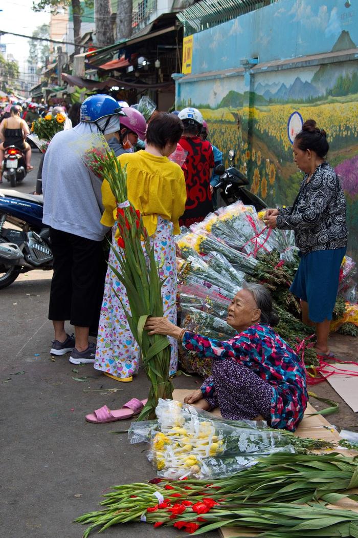 Một bà lão đang cố mời chào bán nốt những khóm Huệ trong thời gian còn ít ỏi của năm cũ