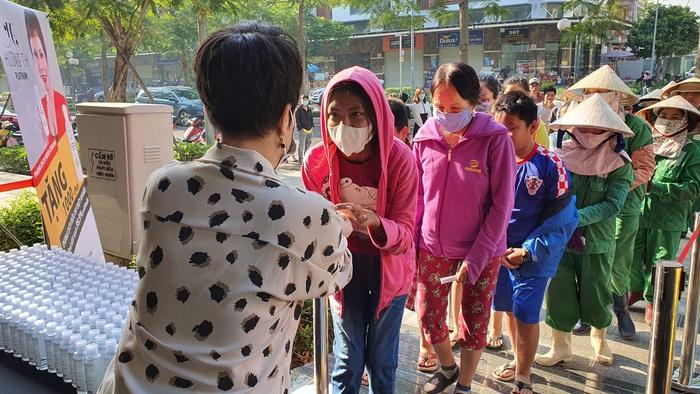 Rất đông người dân đến nhận sản phẩm rửa tay từ nữ nghệ sĩ để phòng tránh bệnh dịch. Ảnh: MT