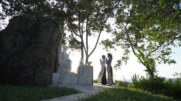 Du khách trước tượng Phật trên đỉnh núi trong Raragon Resort