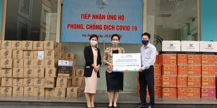 Phó Chủ tịch Hội LHPN Việt Nam Trần Thị Hương (giữa) nhận biển tượng trưng hỗ trợ sản phẩm của Công ty TNHH Nestlé Việt Nam