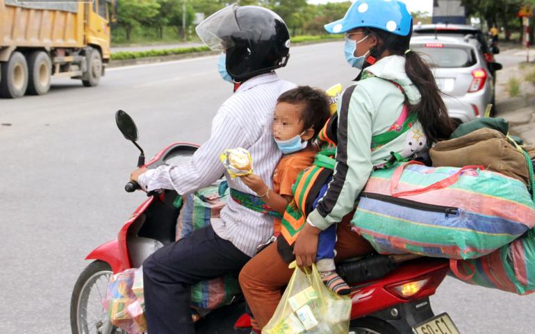 Vợ chồng chị Lầu Y Xồng và con nhỏ vượt hơn nghìn cây số bằng xe máy từ Đồng Nai về Nghệ An. Ảnh: Ngọc Tú