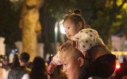 Những em bé theo chân bố mẹ chen giữa 'biển người' đêm Noel Hà Nội